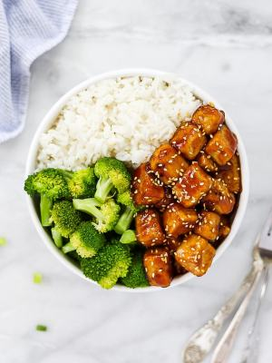 Overhead picture of glazed sesame tofu in a white bowl with rice and broccoli florets.