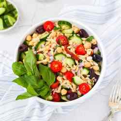 Mediterranean orzo salad with olives, cucumbers, orzo, chickpeas, and tomatoes, garnished with basil.