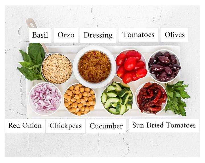 A white platter holding small white bowls of ingredients including: basil, orzo, dressing, tomatoes, olives, red onion, chickpeas, cucumber, sun dried tomato