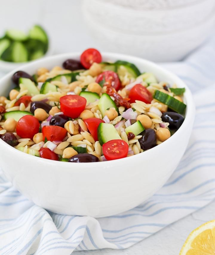 a vertical shot of a white bowl containing vegan orzo salad