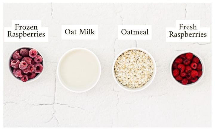 A picture with 4 small white bowls containing ingredients, one with frozen raspberries, one with oat milk, one with oatmeal, and one with fresh raspberries.