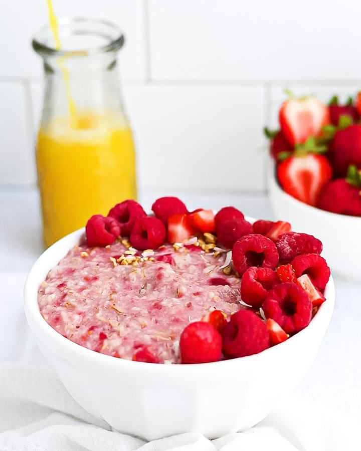 A completed picture of raspberry oatmeal garnish with fruit and granola, orange juice being poured in the background and a bowl of strawberries in the background.