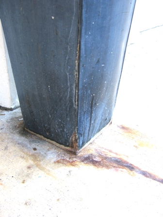 Details of tippy leaking metal planter