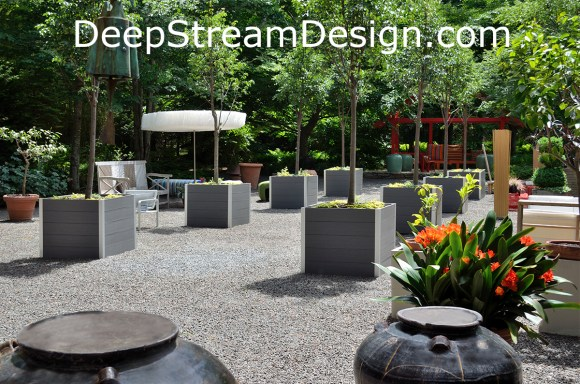 Large square Commercial Wood Planters use maintenance free recycled plastic lumber inside thier aluminum frames to hold rugged liners planted with trees in the forest clearing of the Longhouse Reserve in the Hamptons. Click for info