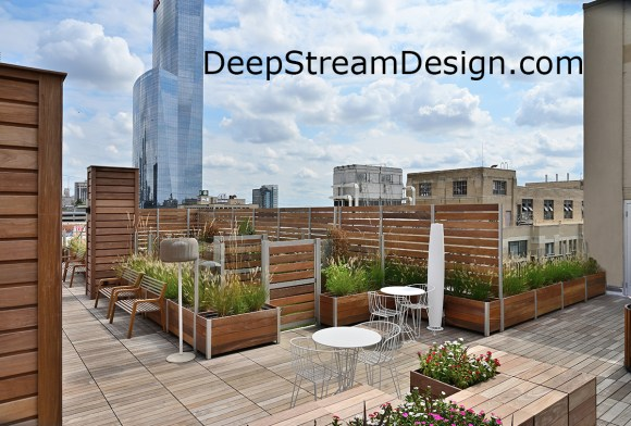 Large multi-section prefabricated modular commercial wood planters with their aluminum frame anchor screen wall, without penetrating there roof, to create a dog park on an urban apartment roof deck. Click for info