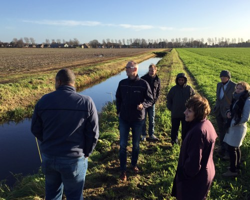 Secretary Ross (center-foreground) visiting Wageningen University's demonstration farm in the Netherlands. CDFA's Science Adviser, Dr. Amrith Gunasekara (in hood), is behind Secretary Ross.