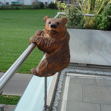 bear sculpture climbing a railing in garden