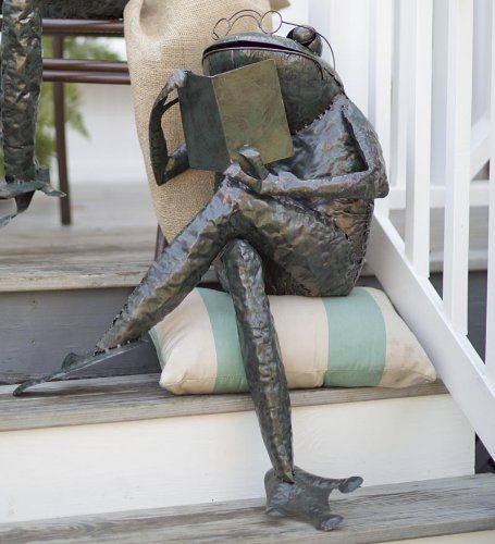small statue frog reading book on a cushion