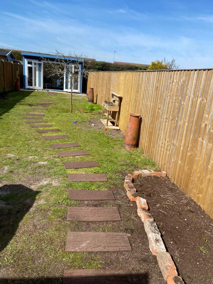 long narrow garden with centre path and garden room at end