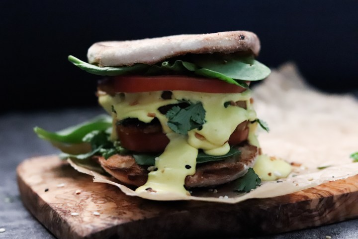 the best vegan eggs benedict breakfast sandwich dripping with plant based hollandaise sauce.