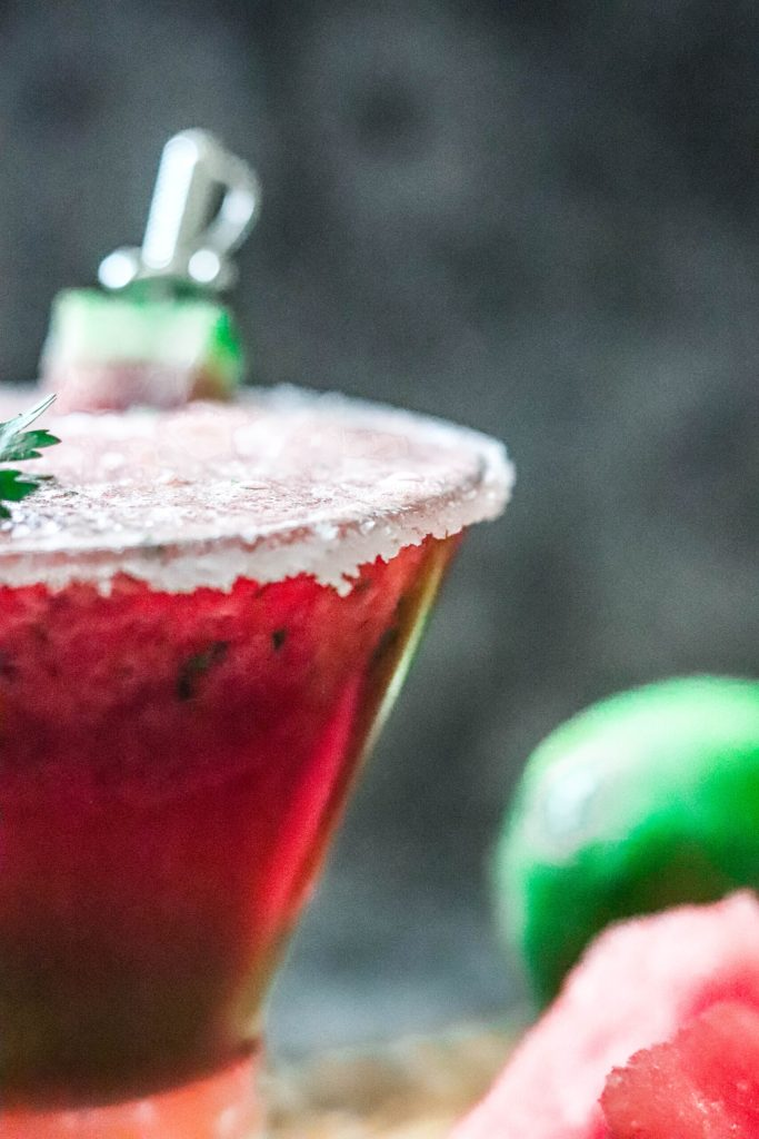Close up photo of a watermelon margarita with a course salted rim.