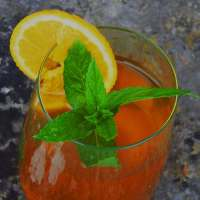 Homemade iced tea with a sprig of mint and a slice of orange