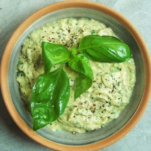 Bowl of hummus garnished with fresh basil leaves