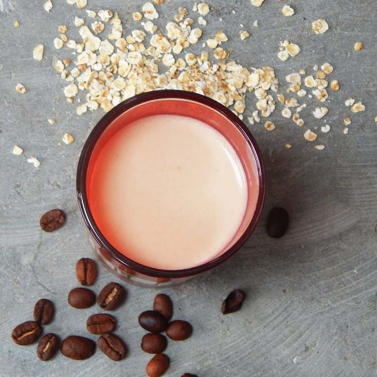 Oat milk in a pink glass with oats and coffee beans scattered nearby