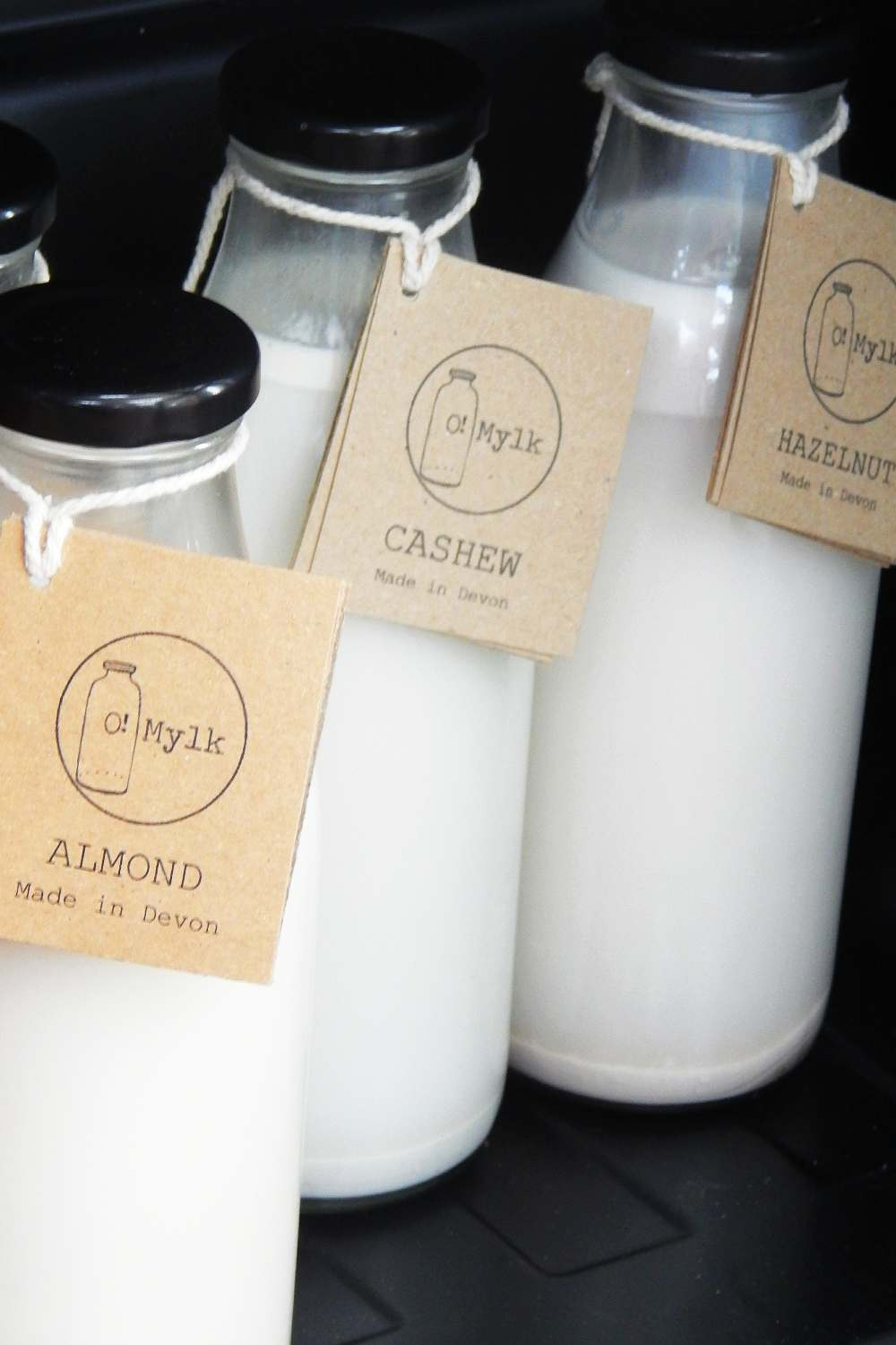 Nut milks in glass jars with cardboard labels tied with string
