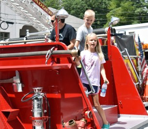 Grey Ward, 6, and his sister Lass Ward, 9, check the view from the back of the fire truck.