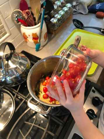 Child pouring tomatoes into pot