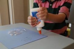 Child gluing handprints
