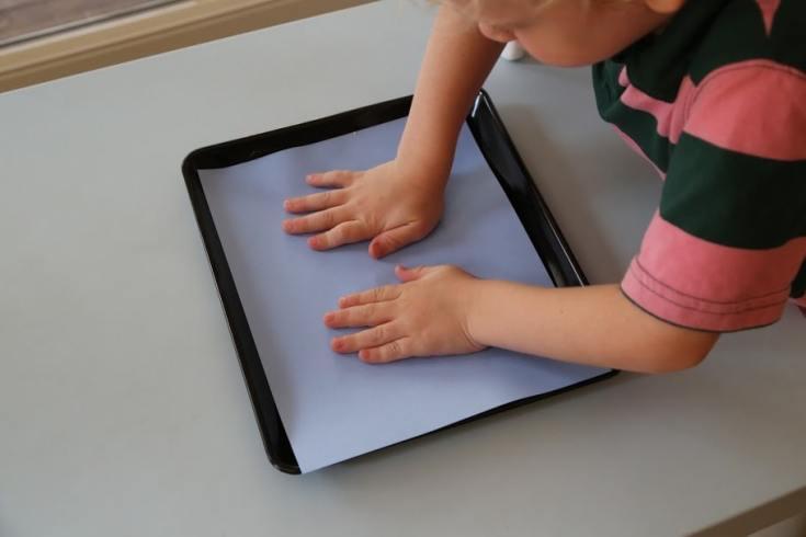 Child pressing handprints into quinoa