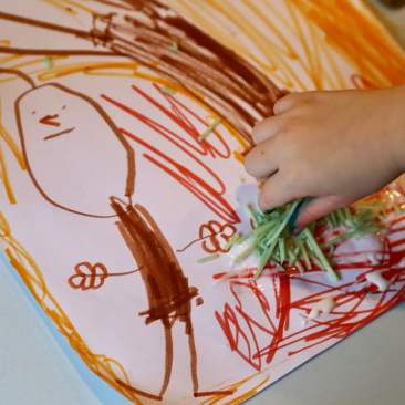 Child gluing parmesan cheese grass on picture