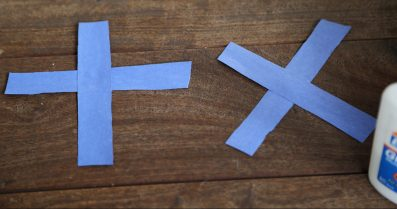 """Blue strips of paper in shape of """"x"""" and """"t"""""""