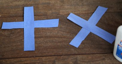 "Blue strips of paper in shape of ""x"" and ""t"""