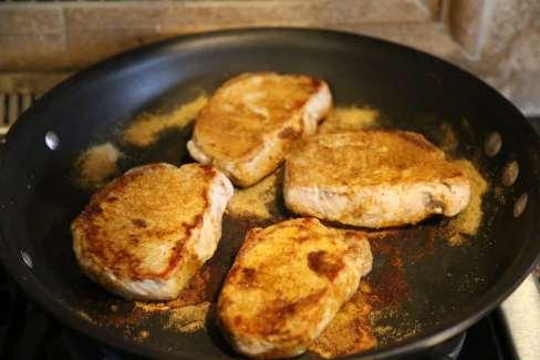 4 pork chops browning in pan