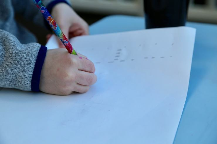 Child writting dashes for letters of name