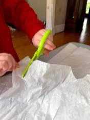 Child cutting white tissue paper