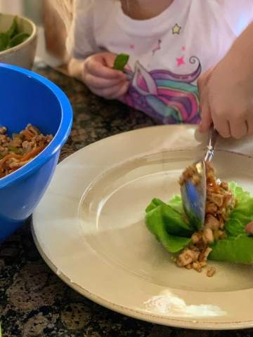 child scopping meat onto lettuce wrap