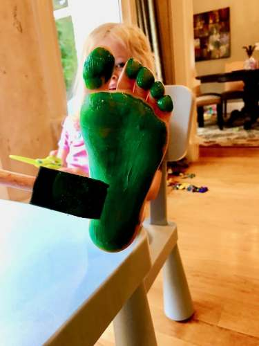 Child painting bottom foot for craft