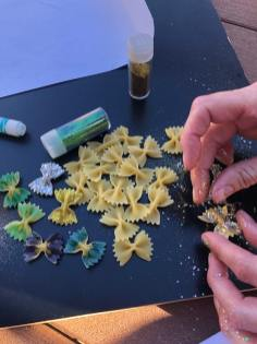 Sprinkling glitter on pasta butterflies