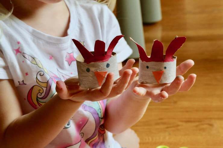 child holding two chicken napkin rings