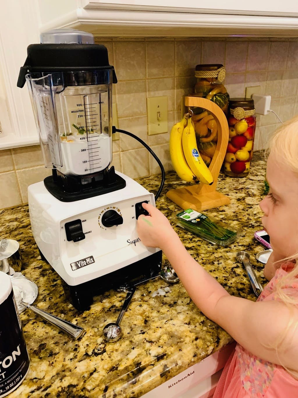 child turning on Vitamix