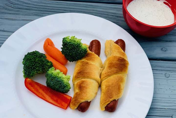 Crescent roll hot dogs on plate with veggies