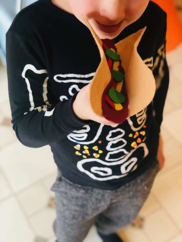 child pretending to eat funny felt hot dog