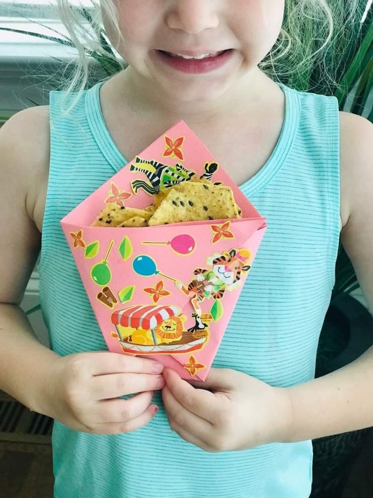 child holding DIY paper chip bag