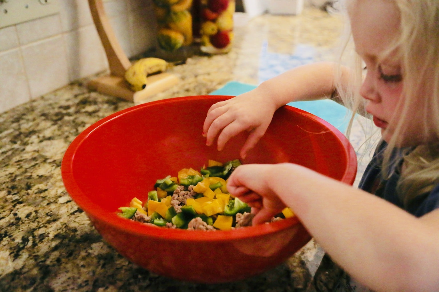 child tasting olives in taco salad bowl