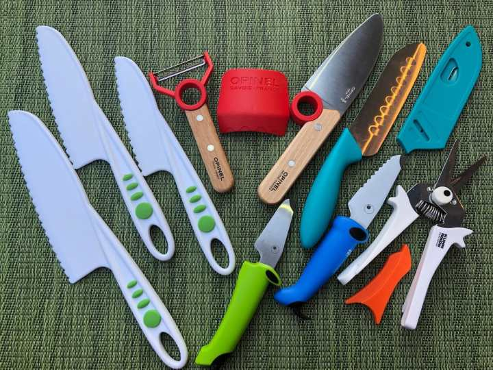 different brands of kids kitchen knives, vegetable peelers, and snippers laid out on a green placement