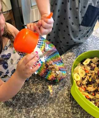 Pouring homemade trail mix into bags