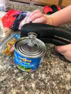 child opening can of green chilis