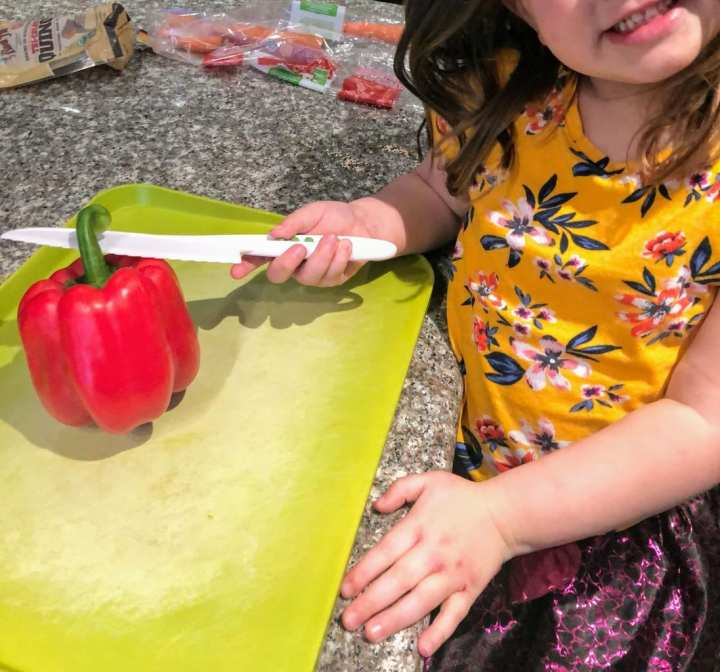 Child cutting red bell pepper