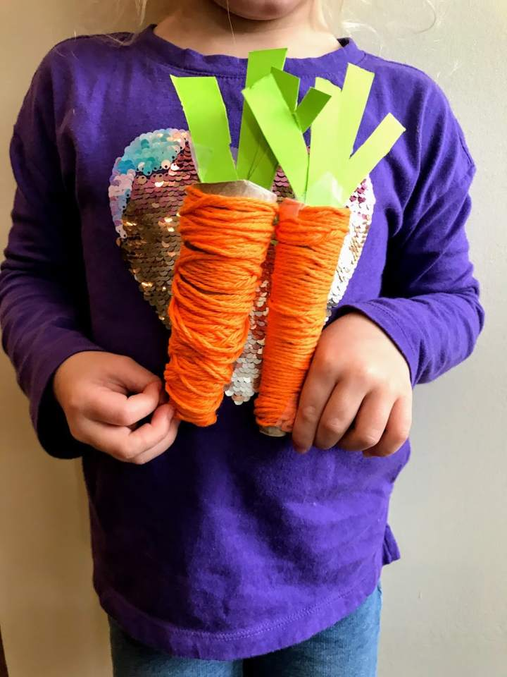 chikd holding play food carrots1.