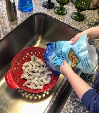 Pouring frozen shrimp into colander