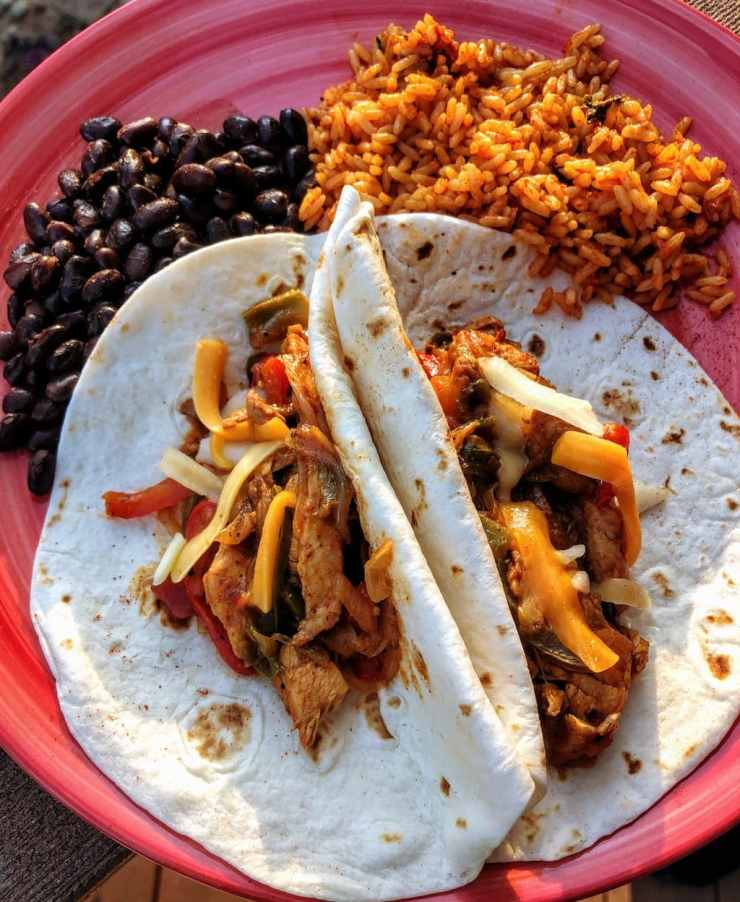 chicken fajitas with cheese, rice and beans on a pink plate