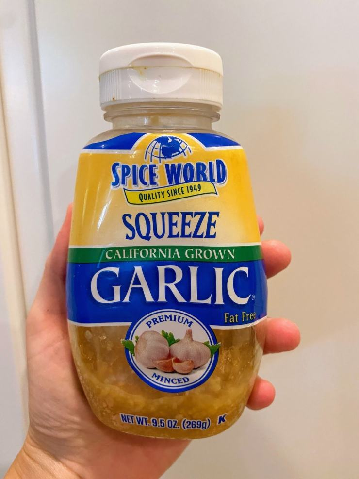 Hand holding a jar of Spice World squeeze garlic