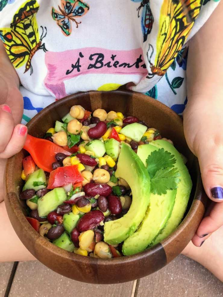 child holding a three bean salad with avocado, on her lap