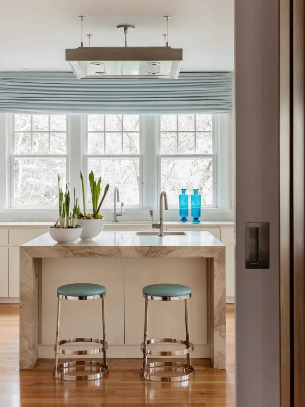 The kitchen island is wrapped in stone and features a prep sink and area as well as bar stools for casual dining. A custom light fixture above provides both general and task lighting.
