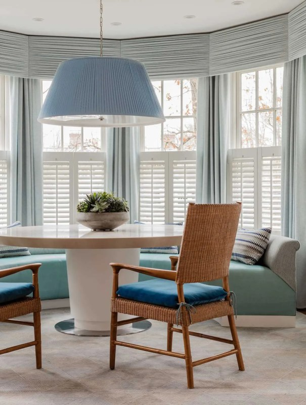 The breakfast nook is inviting with a custom banquette and center pedestal dining table that allows for seating flexibility. Window treatments encircling the nook let in natural light and also offer privacy.