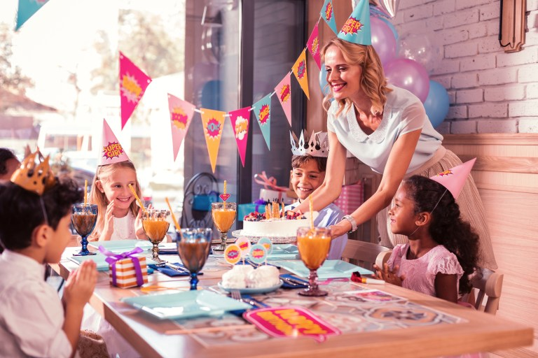All children smiling while kind mother bringing birthday cake
